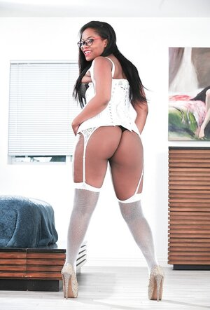 Plumper black babe in white corset and fishnets shoves butt plug into ass hole