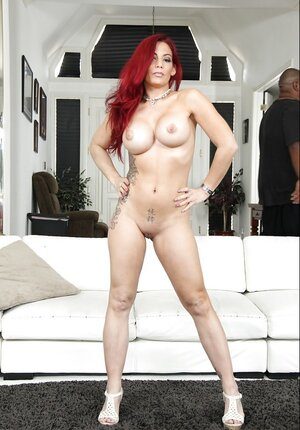 Superior redhead with hefty breasts lies being naked on the white couch