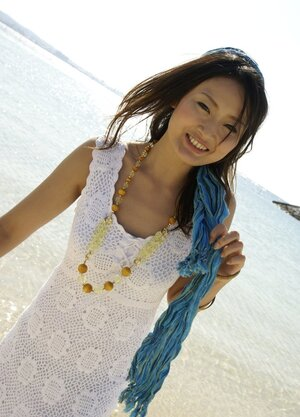 Sweet Japanese girl in white dress walks into the water being dressed