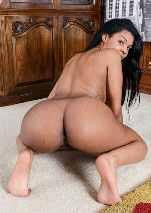 Cheerful Mulatto hussy tirelessly poses on a carpet being wholly undressed