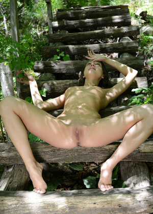 Dame with tiny boobs takes XXX poses in the naked on the wooden steps