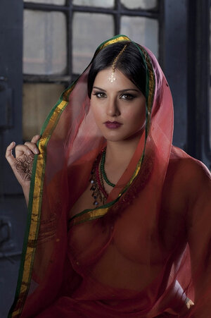 Diva in a transparent red sari fails to hide her sizeable melons with dark nipples
